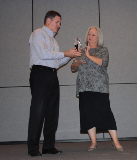 Watkins Wellness President Steve Hammock, left, accepts the Toastmasters International Corporate Recognition Award from District Director Joyce Persichilli.